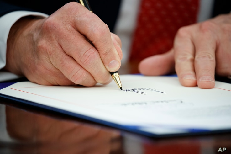President Donald Trump signs an executive order, Feb. 28, 2017, in the Oval Office of the White House in Washington.