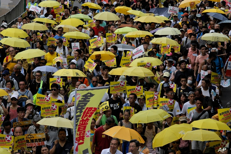 Protesters carry yellow umbrellas during a rally in a downtown street to support for a veto of the government's electoral reform package in Hong Kong, June 14, 2015.