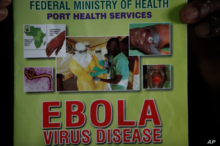 Nigeria health official display a leaflet explaining Ebola Virus Disease at the arrival hall of Murtala Muhammed International Airport in Lagos, Nigeria, Monday, Aug. 4, 2014. Nigerian authorities on Monday confirmed a second case of Ebola in Africa'...