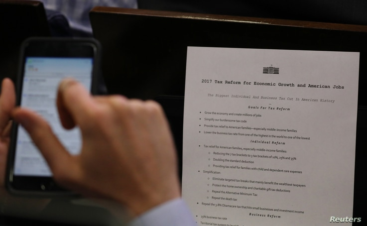 A reporter shoots a picture of a White House press release on its tax reform plan during the daily briefing at the White House in Washington, April 26, 2017.