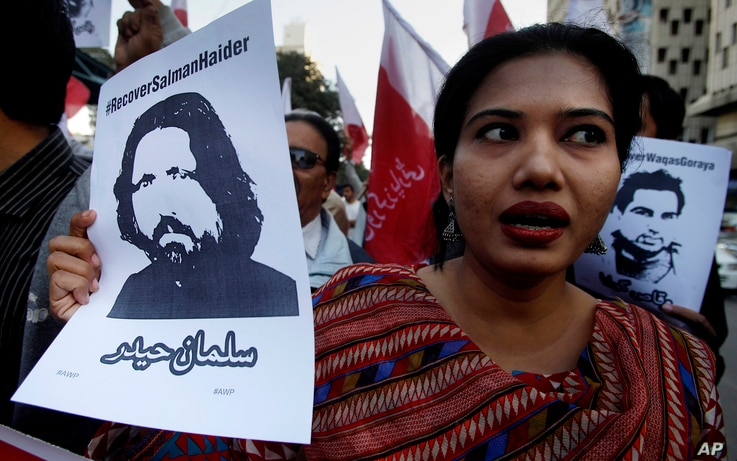 A woman holds a portrait of missing university professor and poet Salman Haider during a rally in support of the activist, in Karachi, Pakistan, Jan. 10, 2017.
