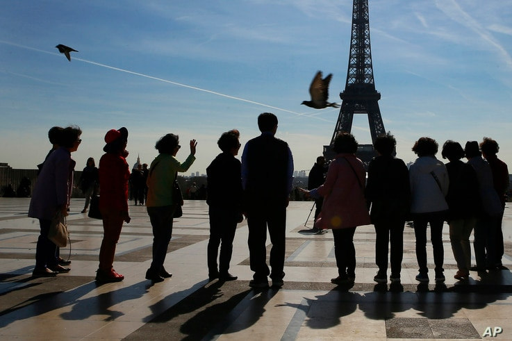 Tourists pose for a souvenir photo on Trocadero with the Eiffel Tower in background on a sunny day in Paris, Thursday, March 30, 2017. France is experiencing heat wave condition with temperatures crossing 22 degrees Celsius (90 Fahrenheit) in several...