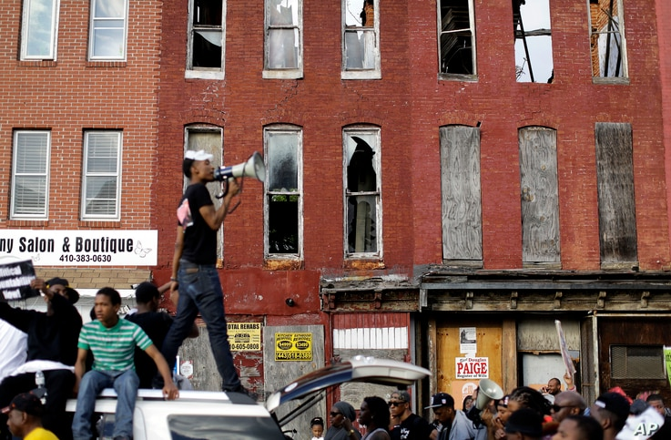 A protester leads marchers in a chant in front of blighted buildings in Baltimore, Maryland, May 2, 2015. A day earlier, charges were announced against six police officers involved in Freddie Gray's death.