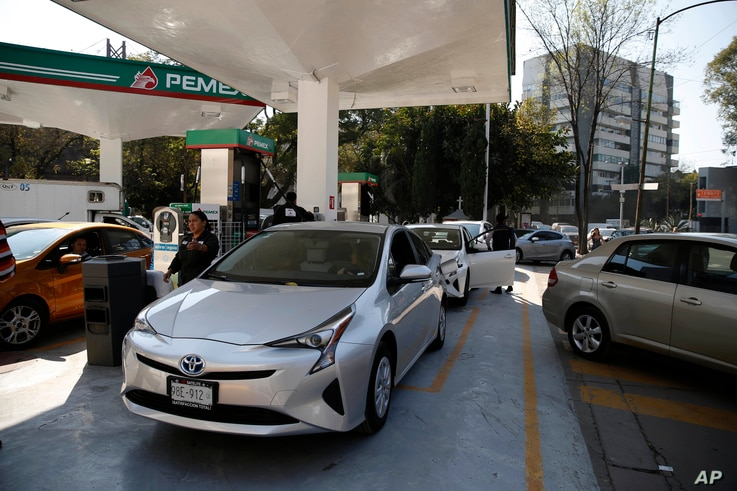 Vehicles stand in line to fill up their fuel tanks at a gas station in Mexico, City, Jan. 8, 2019.