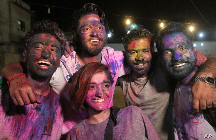 Youth from the Pakistani Hindu community pose with their faces covered with color to celebrate Holi, the festival of colors, at a temple in Karachi, Pakistan, March 12, 2017.