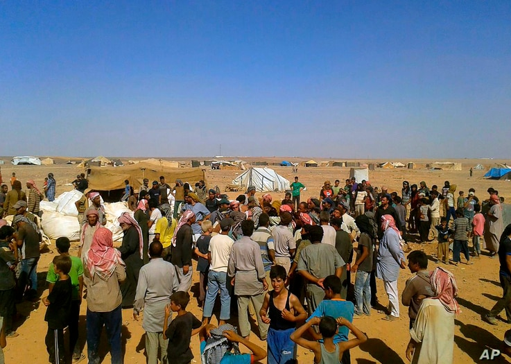 FILE - People gather to take basic foodstuffs and other aid from community leaders charged with distributing equitably the supplies to the Rukban refugee camp on the Jordan-Syria border, Aug. 4, 2016.