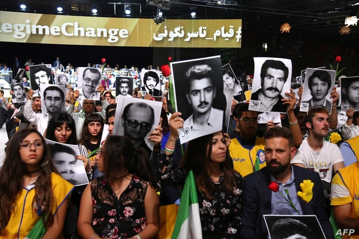 "People hold pictures of relatives killed by the Mohllas regime, during ""Free Iran 2018 - the Alternative"" event, June 30, 2018 in Villepinte, north of Paris during the Iranian resistance national council (CNRI) annual meeting."