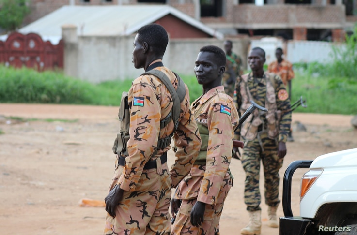 South Sudanese policemen and soldiers stand guard along a street following renewed fighting in South Sudan's capital Juba, July 10, 2016.