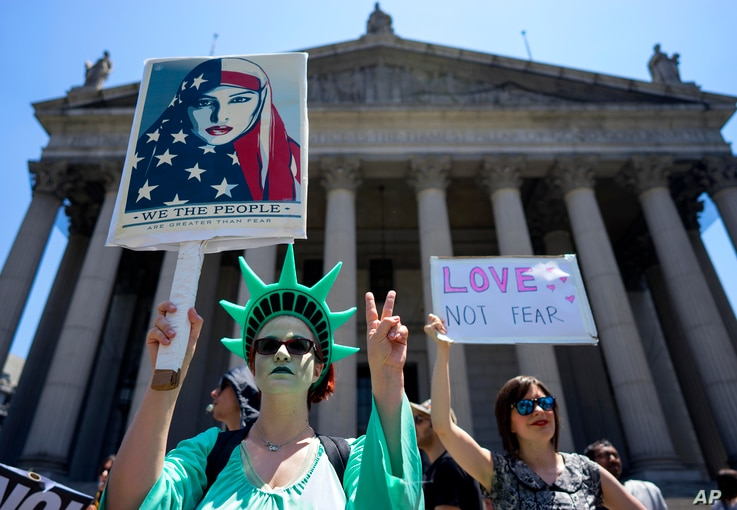 Counter demonstrators opposing a group who gathered across the street to protest against Islamic law, hold signs, June 10, 2017, in New York. In more than two dozen cities across the United States, the group organizing the rallies, ACT for America, i...