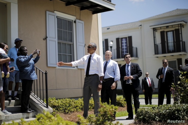 U.S. President Barack Obama chats with local residents of an area reconstructed after Hurricane Katrina, accompanied by New Orleans mayor Mitch Landrieu (3rd R), in New Orleans, Louisiana, Aug. 27, 2015.
