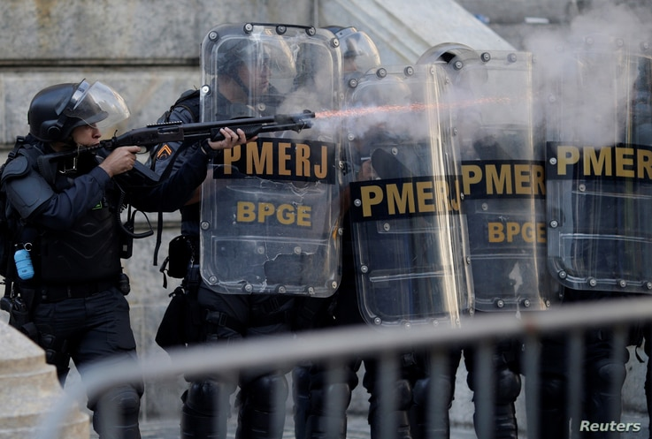 A riot policeman fires rubber bullets during clashes with demonstrators outside the Rio de Janeiro State Assembly in Rio de Janeiro, Brazil, Nov. 17, 2017.