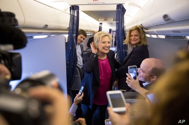 Democratic presidential candidate Hillary Clinton, accompanied by traveling press secretary Nick Merrill, left, and director of communications Jennifer Palmieri, right, listens to a question from a member of the media as her campaign plane prepares t...