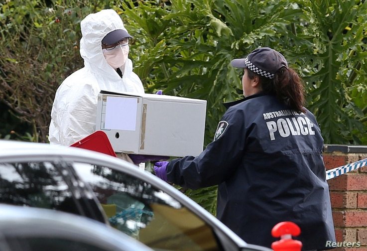 Australian police carry a box from the home of gunman Yacqub Khayre, who was shot dead by police on June 5, 2017, after he shot a man dead and held a woman hostage in the Melbourne suburb of Roxburgh Park in Australia.