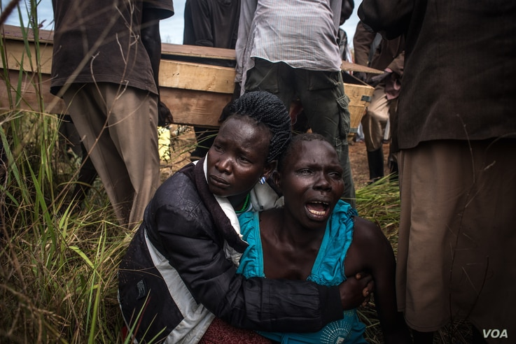 The sister of Duku Evans  — who was killed November 3 amid fighting between government troops and rebels in Logo displaced persons camp in Kajo Keji, South Sudan — wails as the casket containing her brother's body is carried by at his funeral on ...