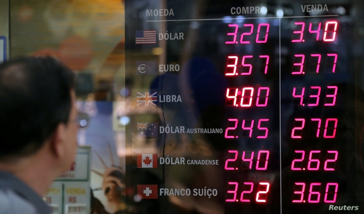 A man observes a board showing the Brazilian Real-U.S. dollar and several other foreign currencies exchange rates in Rio de Janeiro, Brazil, Nov. 9, 2016.