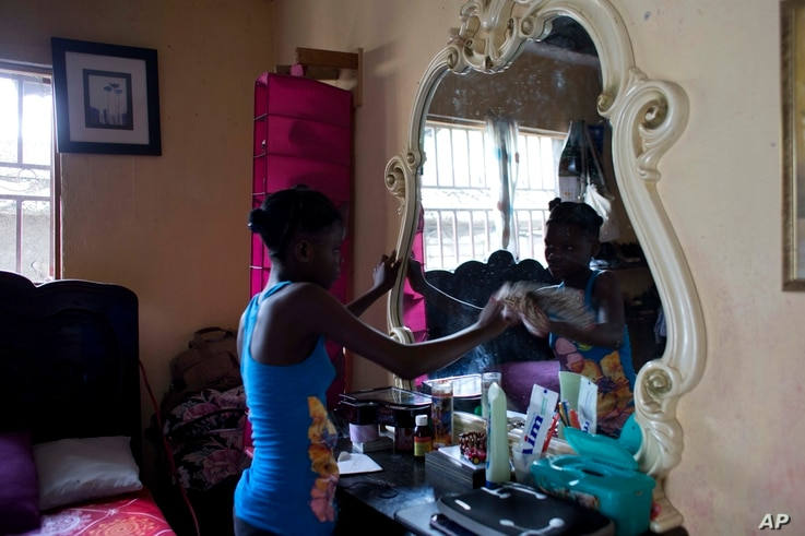 13-year-old Medege Dorlus cleans a mirror at the home she lives in, in Port-au-Prince, Haiti, May 27, 2017.