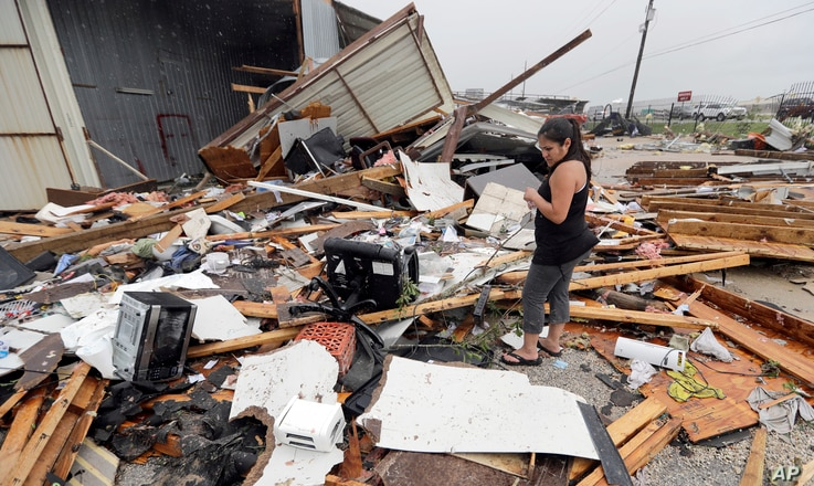 Jennifer Bryant looks over the debris from her family business destroyed by Hurricane Harvey, in Katy, Texas, Aug. 26, 2017.