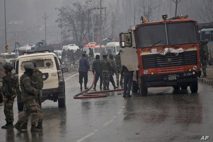 Indian firemen spray water on a road to wash away blood after an explosion in Pampore, Indian-controlled Kashmir, Thursday, Feb. 14, 2019.