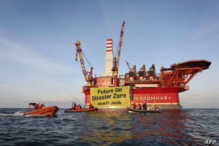 This handout photo taken by Greenpeace on August 25, 2012 shows Greenpeace activists holding a banner in front of the Gazprom 'Prirazlomnaya' oil drilling platform during their protest in the Barents Sea as the Gazprom support boat secures the area. ...