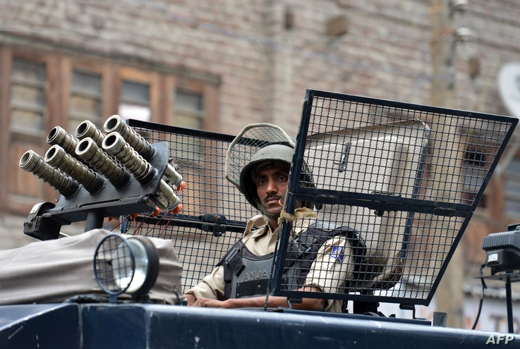 An Indian paramilitary trooper looks out from an armoured vehicle as he takes part in a patrol on a street in Srinagar on August 2, 2016. More than 50 people have been killed and thousands injured in weeks of unrest in Indian-administered Kashmir, sp...
