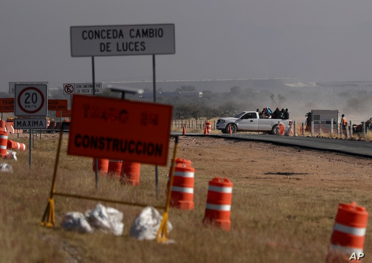 Workers leave the Ford construction site after they were sent home early the day after the U.S. auto company cancelled plans to build its plant in Villa de Reyes, Mexico.