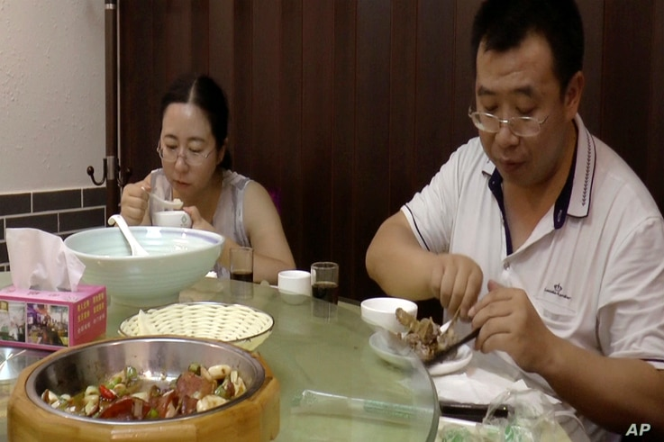 FILE - This image made from  Aug. 1, 2016 video shows Chen Guiqiu, left, has lunch with lawyer Jiang Tianyong after attending a trial for human rights lawyer and activists at the Tianjin No. 2 Intermediate People's Court in Tianjin, China.
