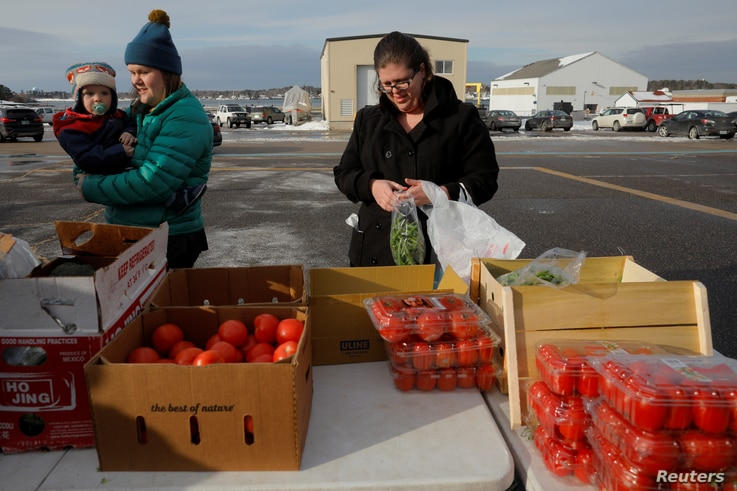 Members of the U.S. Coast Guard working without pay during the government shutdown and their families pick up produce, eggs, milk, bread and other supplies being distributed by Gather food pantry at the U.S. Coast Guard Portsmouth Harbor base in New ...