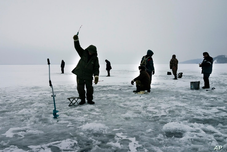 FILE - Ukrainians fish on the thin ice surface of a waterway on the Kiev Reservoir on the Dnipro River on a warm winter's day in the village of Stari Petrivtsi outside Kyiv, Ukraine, Thursday, Jan. 9, 2016.