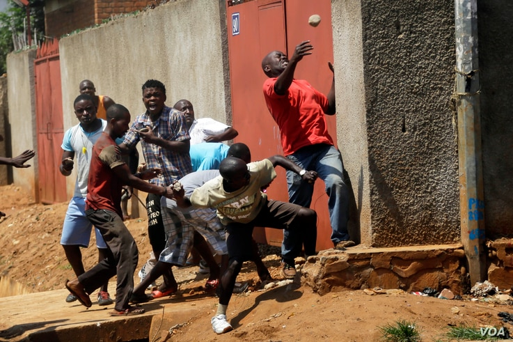 Protester throw stones at police during clashes in the Nyakabyga neighborhood of Bujumbura, Burundi, Thursday May 21, 2015. Protests continue against the  President's decision to seek a third term.  (AP Photo/Jerome Delay)