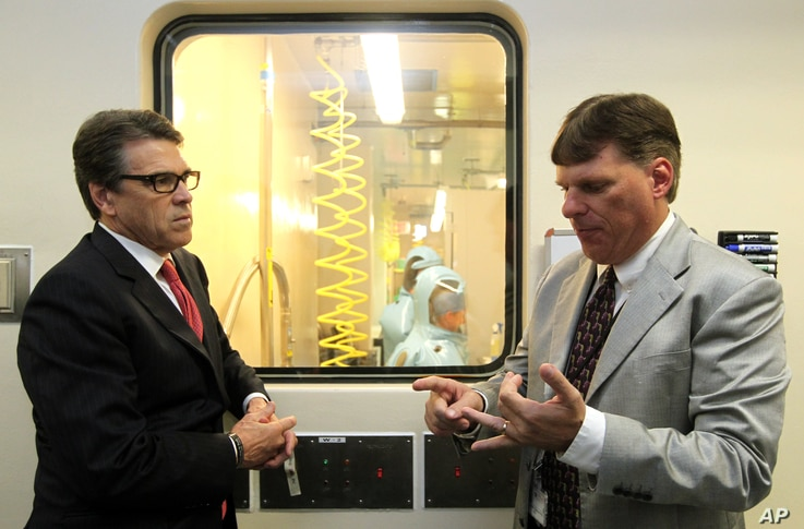 FILE - Tom Geisbert, right, a professor of Microbiology and Immunology at the University of Texas Medical Branch, explains to Texas Gov. Rick Perry the work researchers are conducting in a Bio Safety Level 4 lab in the Galveston National Laboratory, ...