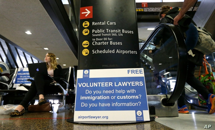 Asti Gallina (left) a volunteer law student from the University of Washington, sits at a station near where passengers arrive on international flights at Seattle-Tacoma International Airport, Feb. 28, 2017, in Seattle. Airport officials and civil rig...