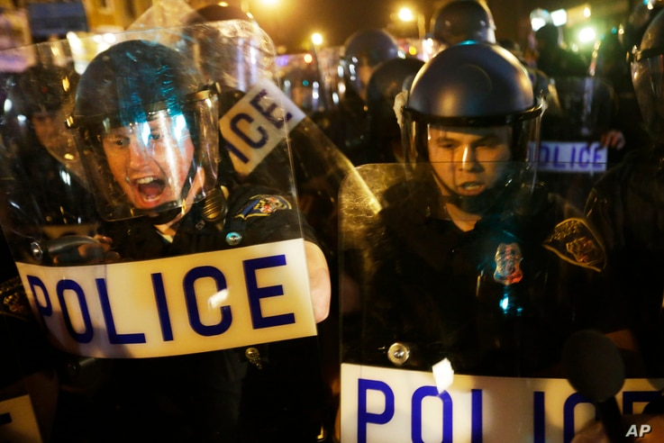 Police in riot gear push back on media and a crowd gathering in the street after a 10 p.m. curfew went into effect Thursday, April 30, 2015.
