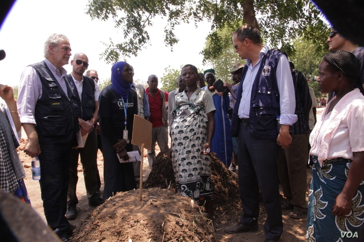 EU Commissioner Christos Stylianides (L) learns about a manure re-purposing initiative launched by the local community in Chikwawa district. (L. Masina/VOA)