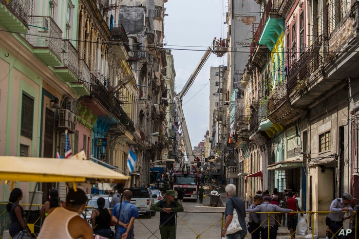Passersby watch as residents are rescued by firemen in a basket crane from a building in which the interior staircase collapsed leaving dozens trapped, in Havana, Cuba, April 19, 2017.