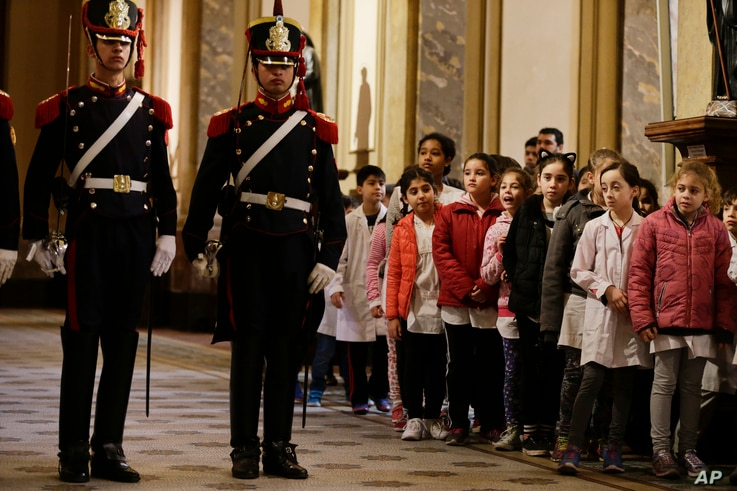 Schoolchildren look at soldiers moments before the arrival of U.S. Vice President Mike Pence at the Buenos Aires Metropolitan Cathedral in Argentina, Aug. 15, 2017. Pence participated in a wreath-laying ceremony to commemorate Jose de San Martin, an ...