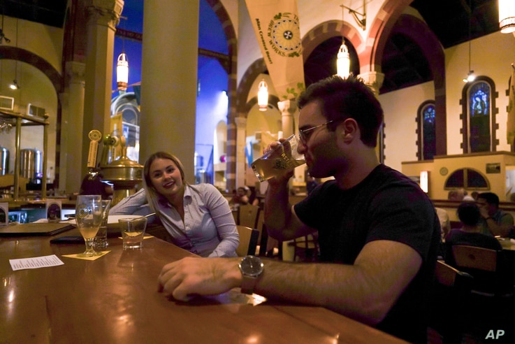 FILE - Jesse Hulien, right, drinks a beer as Molly Hartman, left, looks on, at the Church Brew Works, a former church renovated into a brewery, in Pittsburgh, Aug. 7, 2017.