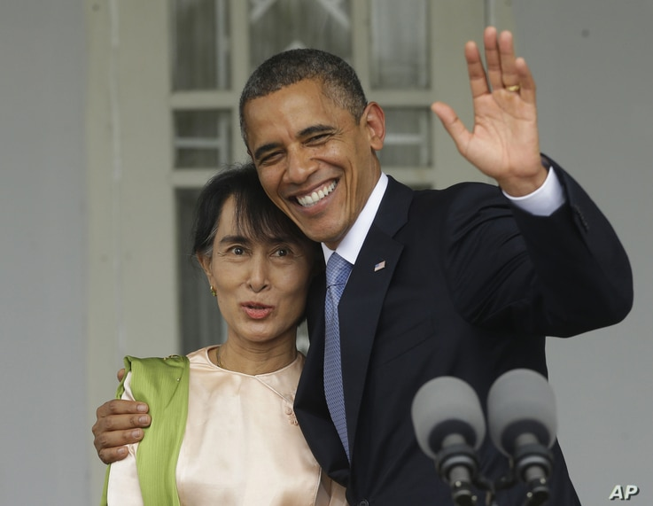 US President Barack Obama, right, waves as he embraces Burmese democracy activist Aung San Suu Kyi after addressing members of the media at Suu Kyi's residence in Rangoon, Burma, November 19, 2012.