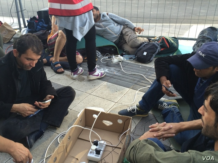 Smartphones help migrants determine routes and sustain vital connections. Aid workers have set up charging stations for them in Vienna, Austria. (Heather Murdock/VOA).