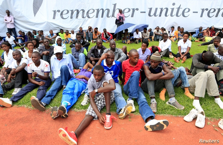 People follow the proceedings of the 20th anniversary commemoration of the Rwandan genocide, in Kigali April 7, 2014.