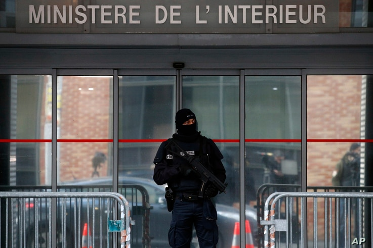 A police officer stands guard in front of the central office for the fight against corruption, financial and fiscal crime (OCLCIFF) where former French President Nicolas Sarkozy was held, in Nanterre, outside Paris, March 21, 2018.
