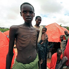 An internally displaced Somali family stand in front of their makeshift shelter in south Mogadishu in Hodan district August 2, 2011