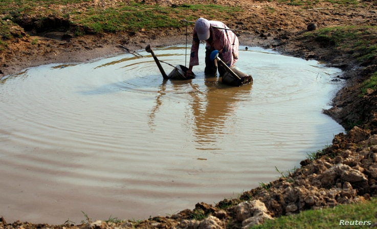 A Cambodian farmer collects water