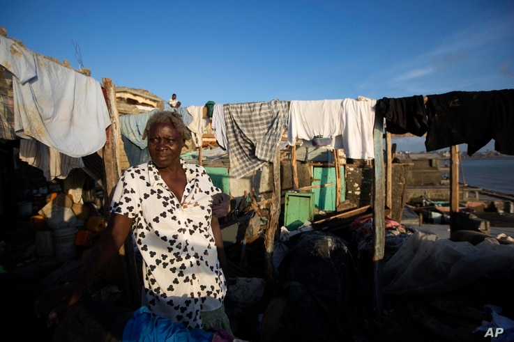 Yolaine Casimir stands in her destroyed house caused by Hurricane Matthew, in Jeremie, Haiti, Oct. 8, 2016.