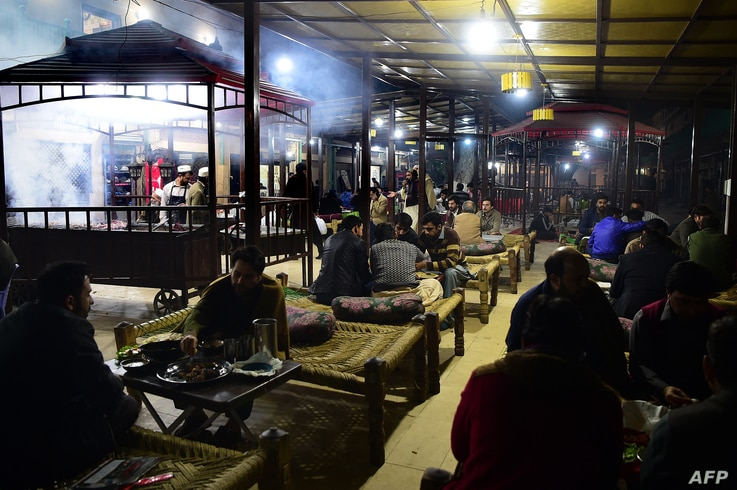 Pakistani patrons enjoy eating grilled meat cooked on a barbeque at the Charsi (Hashish) Tikka restaurant in Namak Mandi in Peshawar, Dec. 6, 2018.