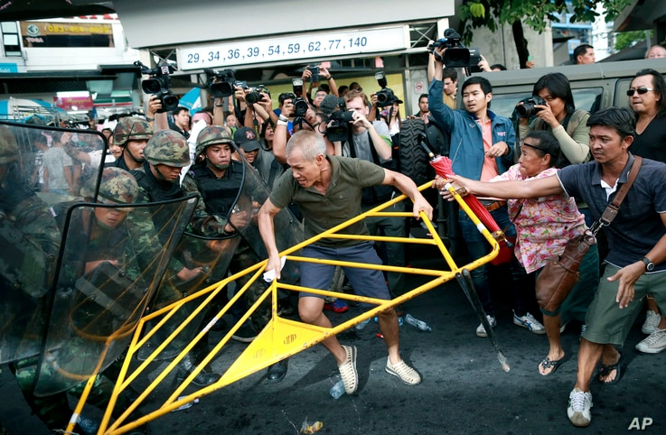 Protesters scuffle with Thai soldiers during an anti-coup demonstration at the Victory Monument in Bangkok, Thailand, May 28, 2014.