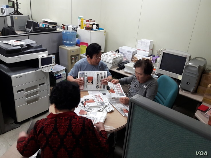 North Korean defectors, working for FreeNK newspaper in South Korea, wrap editions of paper in plastic, ready for the air drop. (Photo: FreeNK)