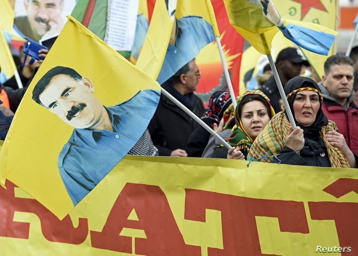 Pro-Kurdish demonstrators carry a flag showing Abdullah Ocalan, the jailed leader of the Kurdistan Workers' Party, as they protest against Turkish authorities during the spring festival of Newroz celebrations in downtown Hanover, Germany, March 19, 2...