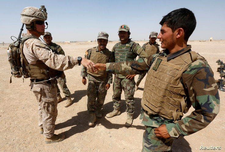 FILE - A U.S. Marine shakes hands with Afghan National Army (ANA) soldiers during a training exercise in Helmand province, Afghanistan, July 5, 2017. Helmand was the scene of an errant U.S. drone strike Friday.