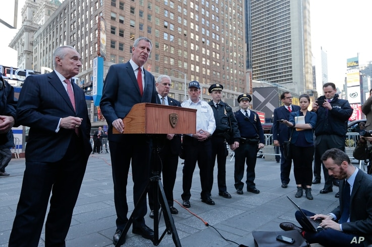New York City Police Commissioner Bill Bratton, left, listens as New York City Mayor Bill de Blasio speaks during a news conference in Times Square about security enhancements in the city, March 22, 2016.