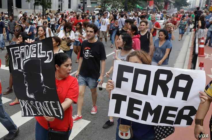 """Demonstrators march with a sign that says in Portuguese """"Get out Temer"""" and a drawing of Cuba's late President Fidel Castro, as they demand the impeachment of Brazil's President Michel Temer in Sao Paulo, Brazil, Nov. 27, 2016."""